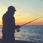 man holding rod in sunset