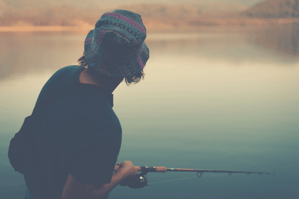 person fishing with spinning reel